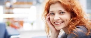 invisalign-woodland-parkd-colorado-smiling-woman-with-red-hair