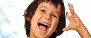 Woodland Park Orthodontics Happy child indoor with hand gesture