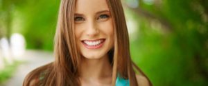 clear-braces-woodland-park-smiling-woman-green-backgroun